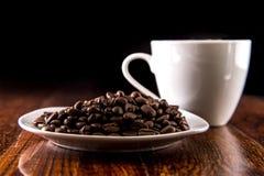 Kaffeebohnen auf weißer Platte mit Kaffeetasse Stockbild