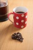 Kaffeebohnen, Cafetiere und roter pickeliger Becher Stockfotografie