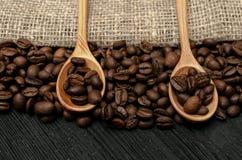 Kaffeebohnen in den hölzernen Löffelschaufeln auf dem Tisch lizenzfreie stockbilder