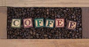 Kaffeebohnen in den Kaffeebohnen einer Holzkiste mit hölzernem auf Text ist Kaffee Stockfotos