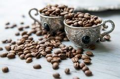 Kaffeebohnen in den silbernen Weinleseschalen auf hölzernem Hintergrund Lizenzfreies Stockbild