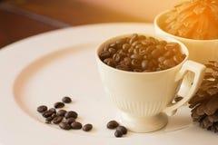 Kaffeebohnen in der Schale auf weißer Platte mit warmem Lichteffekt, vint Stockbild