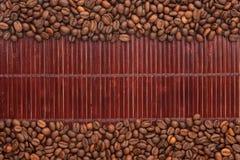 Kaffeebohnen, die auf einer Bambusmatte liegen Lizenzfreie Stockfotografie