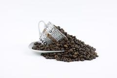 Kaffeebohnen, die aus einem Becher heraus gießen Lizenzfreie Stockbilder