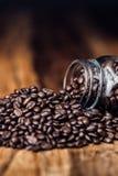 Kaffeebohnen, die aus Glas heraus verschüttet werden stockbilder