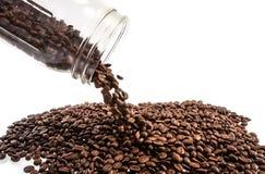 Kaffeebohnen, die heraus Glasflasche verschütten stockfotografie