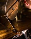 Kaffeebohnen, die von der antiken Zufuhrmaschine ab 1900 fallen stockfotos
