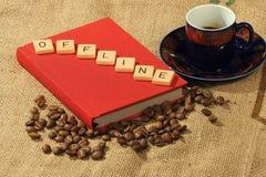 Kaffeebohnen, eine aufwändige Schale, ein rotes Buch und die Buchstaben off-line auf einem Hintergrund des groben Sackzeugs Stockbilder