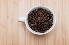 Kaffeebohnen in einem Becher Stockfotos