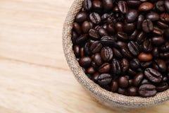Kaffeebohnen in einem kleinen kleinen Holz des Sacks auf dem Tisch Lizenzfreies Stockbild