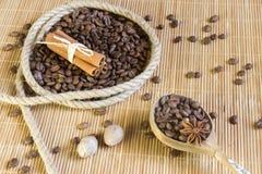 Kaffeebohnen in einem Ring des Hanfs, Sternanis auf der Hintergrundbambus Matte Nahe bei dem hölzernen Löffel mit Jamaikapfeffer lizenzfreie stockfotografie