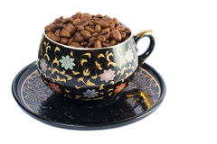Kaffeebohnen in einer kleinen Schale auf einer Untertasse auf einem weißen Hintergrund Getrennt Stockfotos