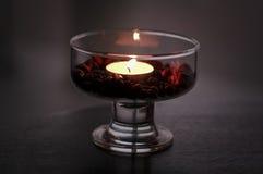 Kaffeebohnen in einer Schale mit einer Kerze Stockbilder