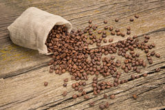 Kaffeebohnen in einer Tasche auf Brettern Lizenzfreie Stockbilder