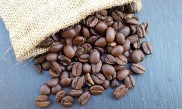 Kaffeebohnen in einer Tasche auf dunklem Steinhintergrund Stockbilder