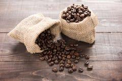 Kaffeebohnen in einer Tasche auf hölzernem Hintergrund Stockbild
