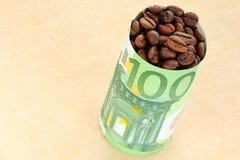Kaffeebohnen eingewickelt mit Banknote Stockbilder