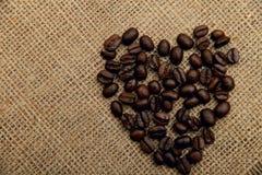 Kaffeebohnen in Form eines Herzens auf einer Serviette des natürlichen Leinwandhintergrundes stockbild