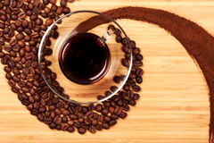 Kaffeebohnen in Form eines Strudels mit Glas Lizenzfreies Stockfoto