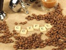 Kaffeebohnen, Glasbecher, Besetzer vor einem Gruppengriff mit dem Buchstabekaffee auf einem Hintergrund des groben Sackzeugs Stockfoto