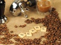 Kaffeebohnen, Glasbecher, Besetzer vor einem Gruppengriff mit den Buchstabebohnen auf einem Hintergrund des groben Sackzeugs Stockfotos