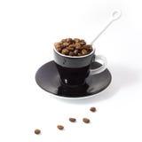 Kaffeebohnen im Espresso Cup und dem Saucer lizenzfreies stockbild