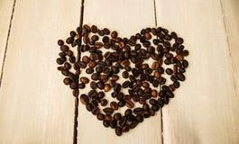 Kaffeebohnen im Herzen auf hölzernem Brett Lizenzfreie Stockfotos