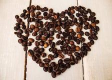Kaffeebohnen im Herzen auf hölzernem Brett Lizenzfreies Stockfoto
