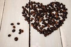 Kaffeebohnen im Herzen auf hölzernem Brett Stockfotografie
