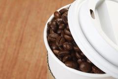Kaffeebohnen im Papiercup lizenzfreie stockbilder