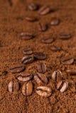 Kaffeebohnen Makro auf Hintergrund des gemahlenen Kaffees Stockfoto