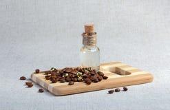 Kaffeebohnen, Massageöl in einer speziellen Glasflasche Stockfoto