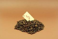 Kaffeebohnen mit Dollarzeichen-Braunhintergrund Stockbild