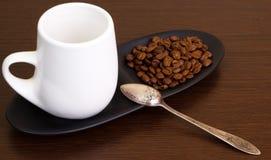 Kaffeebohnen mit einem Kaffee im weißen Cup Stockfotografie