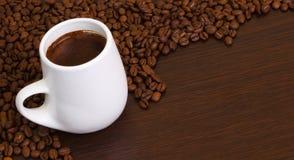 Kaffeebohnen mit einem Kaffee im weißen Cup Lizenzfreie Stockbilder