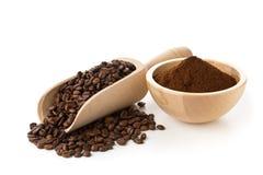 Kaffeebohnen mit gemahlenem Kaffee in der hölzernen Schüssel Lizenzfreies Stockfoto