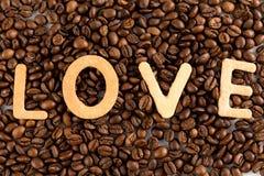Kaffeebohnen mit Plätzchen in Form des Liebeswortes Stockbild