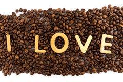 Kaffeebohnen mit Plätzchen in Form des Liebeswortes Stockfotografie