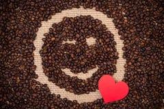 Kaffeebohnen mit rotem Herzen und dem Blinzeln des smileygesichtes Stockfoto