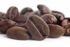 Kaffeebohnen schließen oben in getrenntem weißem Hintergrund Lizenzfreies Stockfoto