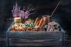 Kaffeebohnen, Schokolade, Zimt, Sternanis und Honig in einer Holzkiste lizenzfreies stockbild