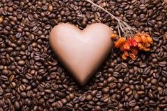 Kaffeebohnen tapezieren mit Schokoladenherzen und Viburnum berrie lizenzfreies stockbild