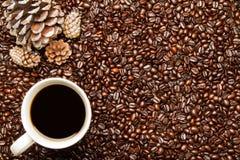Kaffeebohnen u. Kaffeetasse mit Feiertags-Kiefern-Kegeln Stockfotografie