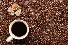 Kaffeebohnen u. Kaffeetasse mit Feiertags-Kiefern-Kegeln Stockfoto