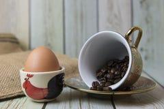 Kaffeebohnen und Ei auf dem Tisch (Stilllebenart) Stockfoto