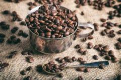 Kaffeebohnen und eine Schale auf einer Leinwand Lizenzfreies Stockbild