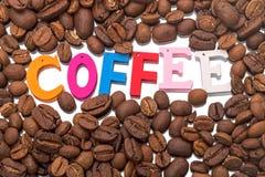 Kaffeebohnen und einziges Wort Lizenzfreie Stockfotos