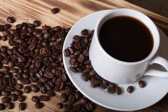 Kaffeebohnen und Kaffee in der weißen Schale auf Holztisch für backgro Lizenzfreie Stockbilder