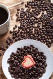 Kaffeebohnen und Kaffee in der weißen Schale auf Holztisch für backgro Stockbild