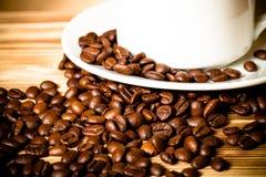 Kaffeebohnen und Kaffee in der weißen Schale auf Holztisch für backgro Stockfotografie
